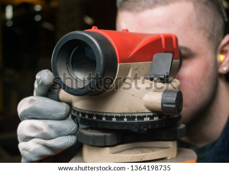 Engineers Automatic Optical Level measure device in a factory. A man looking through the laser measuring tool inside a factory setting. workshop construction tools. #1364198735