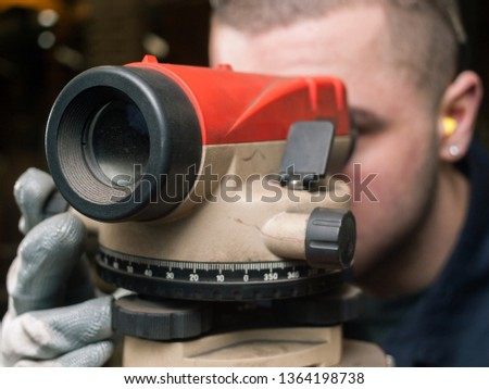 Engineers Automatic Optical Level measure device in a factory. A man looking through the laser measuring tool inside a factory setting. workshop construction tools. #1364198738