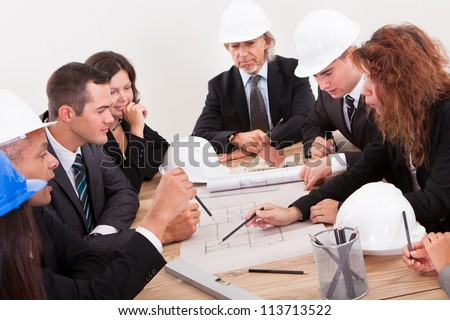 Engineers Discussing About A New Project Around A Table Pointing At A Section On The Blueprint
