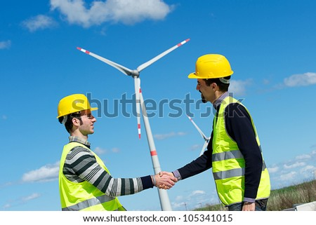 Engineers giving Handshake in a Wind Turbine Power Station Italy