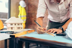 engineers holding a pen pointing to a building and  drawing outlay construction plan as guide for builders with details