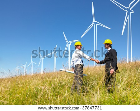Engineers in field with plans building windmills