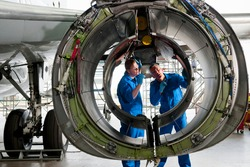 Engineers in uniforms inspecting the engine casing of a passenger jet at a hangar.