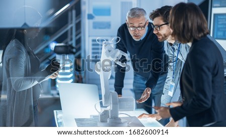 Engineers Meeting in Robotic Research Laboratory: Engineers, Scientists and Developers Gathered Around Illuminated Conference Table, Talking, Using Tablet and Analysing Design of Industrial Robot Arm