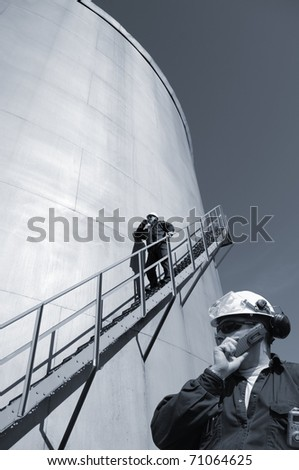 engineers, oil-workers and large fuel-storage tank, inside oil and gas refinery