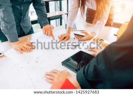 engineers pointing to building on blueprint to drawing design building Project in office, construction concept. Engineer concept