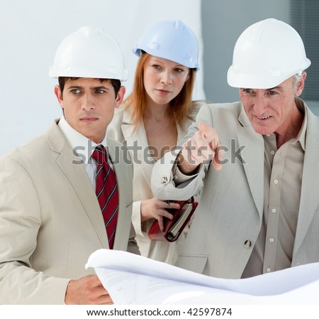 Engineers studying blueprints in a building site