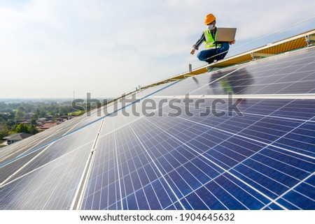 Engineers use a laptop computer to examine the solar panels at a power plant installed with solar panels using solar energy.