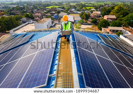 Engineers use a laptop computer to examine the solar panels on the roof of a house where the solar panels are installed using solar energy.