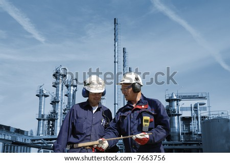 engineers wearing hard-hats in front of oil and gas refinery, background in blue toning