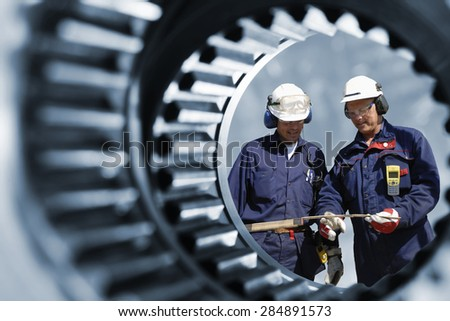 engineers, workers seen through a giant cogwheel and gear axle #284891573