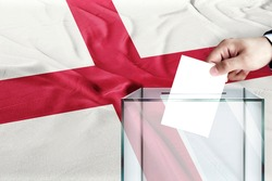 england flag, england  the symbol of elections Male hand puts down a white sheet of paper with a mark as a symbol of a ballot paper against the background