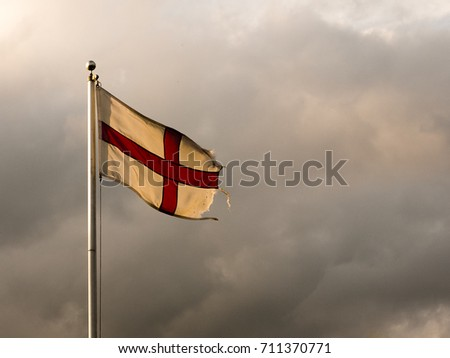 England flag flying in the sky on a pole, dramatic overcast; Essex; England; UK #711370771