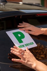 England, UK. 2021.  New driver, young attractive woman holding a green new driver sign to display on her car after passing the driving test.