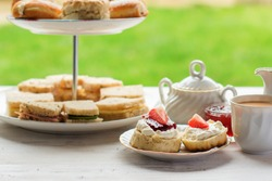 English afternoon teas in the garden cafe: scones with clotted cream and jam, strawberries, with various sandwiches on the background, selective focus