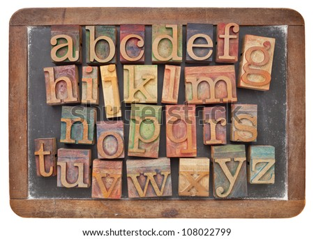 English alphabet in vintage letterpress wood type on an old slate blackboard