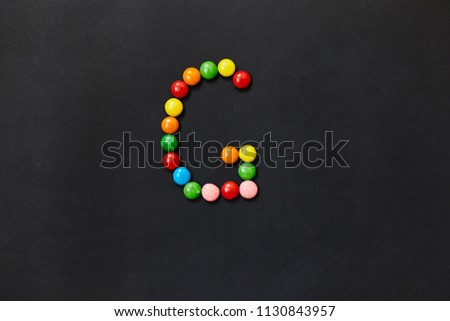 English Alphabet made of colored candies. The letter G. On a black background #1130843957