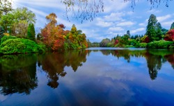 English autumn with Sheffield lake, trees and visible sun rays in Uckfield, East Sussex, United Kingdom