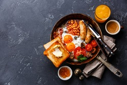 English Breakfast in cooking pan with fried eggs, sausages, bacon, beans, toasts and coffee on dark stone background copy space