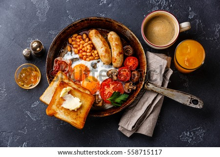 English breakfast in pan with fried eggs, sausages, bacon, beans, toasts and coffee on dark stone background #558715117