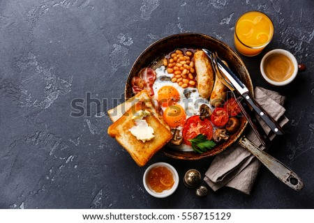 English breakfast in pan with fried eggs, sausages, bacon, beans, toasts and coffee on dark stone background copy space Stock photo ©
