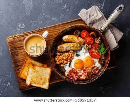 English breakfast in pan with fried eggs, sausages, bacon, beans, toasts and coffee on dark stone background Stock photo ©