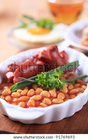 English breakfast of baked beans, sausages, fried egg and bacon