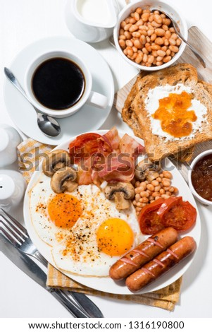 English breakfast of scrambled eggs with bacon, sausages and vegetables on white table, top view Stock photo ©