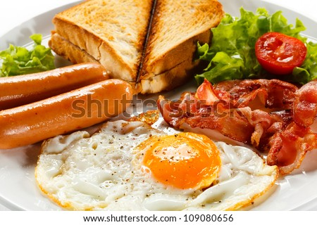 English breakfast - toast, egg, bacon and vegetables on white background