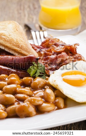 English breakfast with bacon, sausage, fried egg, baked beans and tea or orange juice