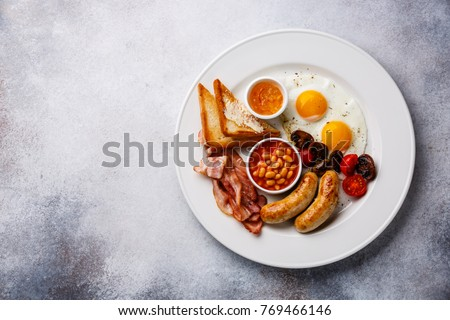 English breakfast with fried egg, sausage, bacon, beans and toast on white background copy space  #769466146