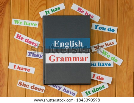 English cards on textbook surrounded by English grammar cards on wooden board Stock photo ©