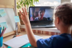 English class with student tutor online. Small schoolgirl studying English language with young native speaker student via internet at home, social distance during quarantine, self-isolation, education