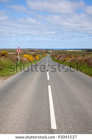 English country road with the sea on the horizon.