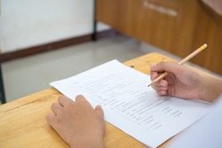 English exams test student in school, university students holding pencil for testing exam writing answer sheet or exercise for taking in assessment paper on table classroom. Education study Concept