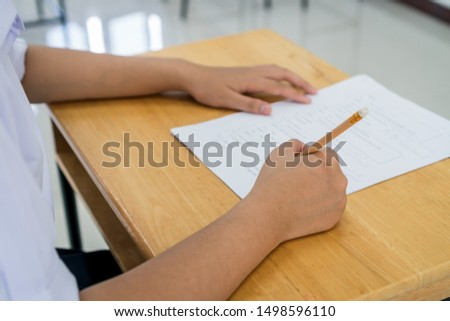 English exams test student in school, university students holding pencil for testing exam writing answer sheet or exercise for taking in assessment paper on table classroom. Education study Concept #1498596110