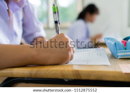 English exams test student in school, university students holding pencil for testing exam writing answer sheet or exercise for taking in assessment paper on table classroom. Education study Concept #1512875552