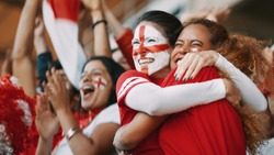 English female soccer fans with England flag painted on their faces hugging each other after their team's victory. English female spectators in football stadium celebrating their team's victory.