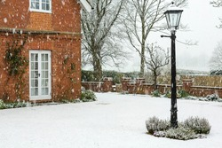 English garden of a country house in winter snow, UK