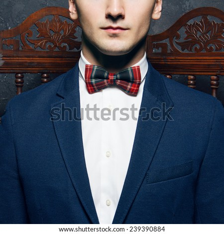 English gentleman beauty concept. Half-face portrait of young man in blue jacket, Scottish bow tie and white shirt posing over vintage screen. Close up. Studio shot