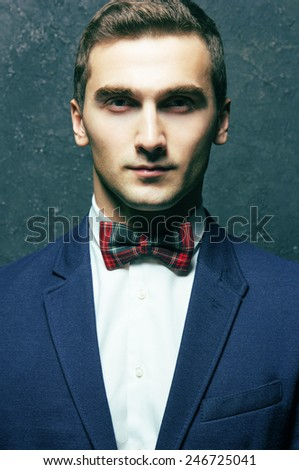 English gentleman beauty concept. Portrait of young and handsome man in blue jacket, Scottish bow-tie and white shirt posing over blue background. Close up. Studio shot