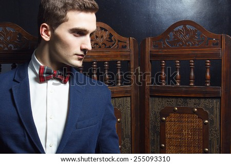English gentleman beauty concept. Portrait of young and handsome man in blue jacket, Scottish bow-tie and white shirt posing over vintage screen. Close up. Studio shot