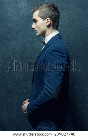 English gentleman male beauty concept. Portrait of fashionable young man in blue casual suit with stylish haircut posing over blue background. Perfect hair & skin. Close up. Studio shot