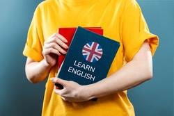English Language Day. A woman holds English textbooks in her hands. Close-up of books. Blue background. The concept of learning foreign languages.