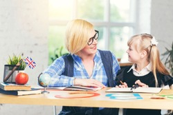 English language female teacher studying with smart kid girl in light white classroom, children learning concept