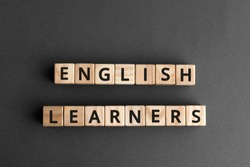 English learners - phrase from wooden blocks with letters, students  english learners concept, top view gray background