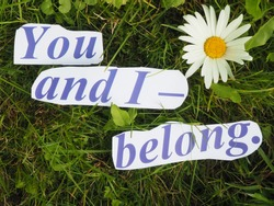 English proverb. an inscription of carved letters on the grass. you and i - belong