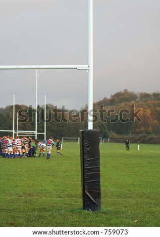 English Rugby, focus on the Goal Posts as trainer gives attention in Background