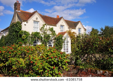 English Rural House and garden with ripening rose-hips growing along the wall
