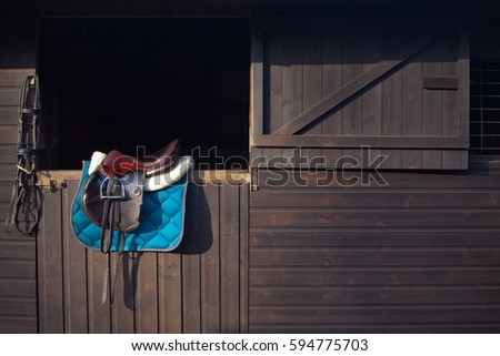 English saddle and bridle hanging on a wooden stable door UK
